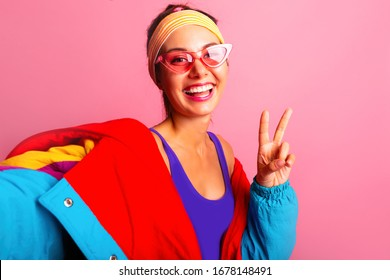 Close up fashion self portrait of Young woman in 90s 80s style clothes on pink background. Selfie Back in time 90s 80s.