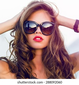 Close up fashion  summer  portrait of stylish  sexy  woman with perfect  tanned fit body   wearing trendy sunglasses drinking cocktail and  enjoying  pool party on luxury villa.