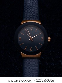 Close up of fashion woman watch, gold and blue color, leather bracelet band. Luxury watches on dark blue background