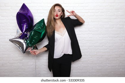 Close up fashionable portrait of cute girl smiling and embracing on white background .Perfect wavy hairstyle. Bright make up. White wall. Party mood,enjoy party,birthday party girl,wear elegant suit