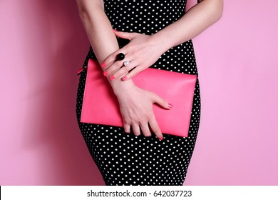 Close up fashionable shapely woman in evening black dress with pink bag in hand. Beautiful accessory ring