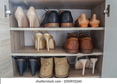 close up fashionable women high heels and leather men shoes in wooden cabinet for going to work