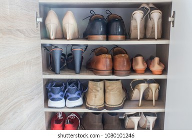 close up fashionable women high heels, leather men shoes and sport shoes in wooden cabinet for going to work