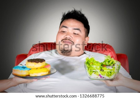 Close up of fat man choosing donuts and rejecting salad while sitting on the sofa