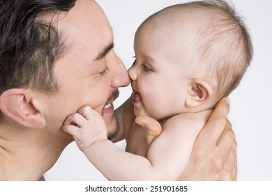 Close up of a father holding his child and smiling at each other.