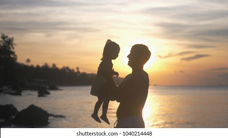 Close up of father throwing up his happy daughter in the air at beautiful sunset