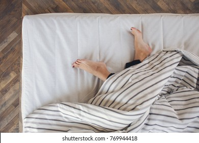 Close up of feet in a bed under blanket. Bare feet of a woman peeking out from under the cover.