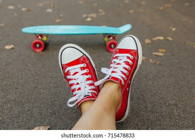 Close up of feet of a girl in red sneakers and blue penny skate board with pink wheels on the background. Urban scene, city life. Sport, fitness lifestyle.