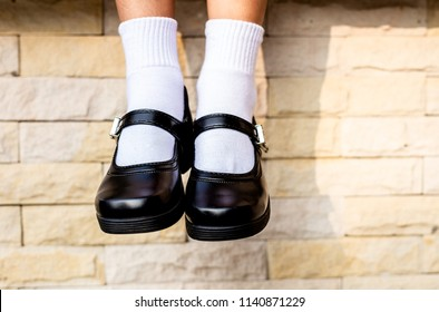 Close up feet of girl wear a black student shoes
