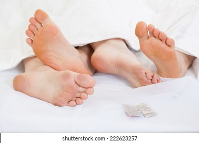 Close up of feet of a happy couple in bed