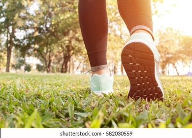 close up of feet of a runner running on grass leaves training for marathon and fitness healthy lifestyle