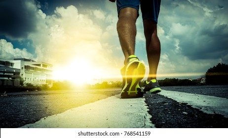 close up feet with running shoes and strong athletic legs of sport man, Athlete man in running pose on city street. Sport tight clothes. Bright sunset