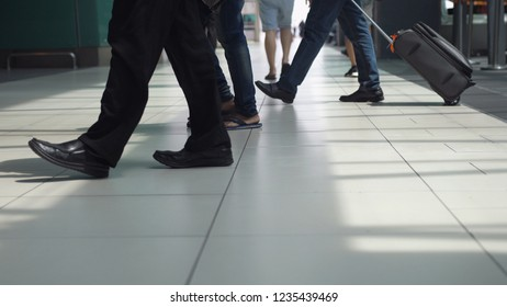 Close up of feet of unrecognizable people with baggages walking in terminal airport