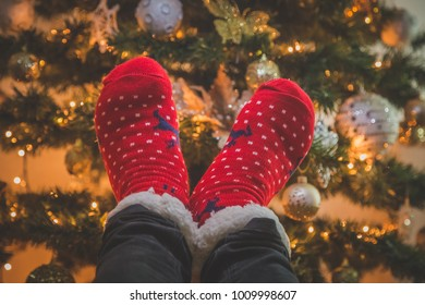 Close up of feet wearing red Christmas socks against decorated Christmas tree background