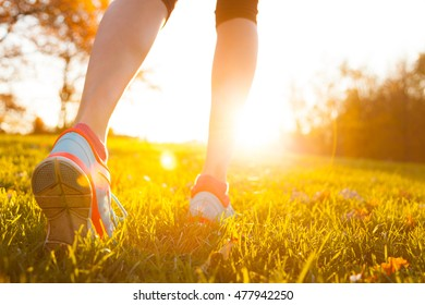 Close up of feet of woman runner running in grass, concept of training exercise
