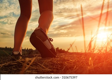 Close up of feet of a woman running in autumn grass against sunset