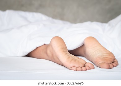 Close up feet of women on white bedding in the morning time