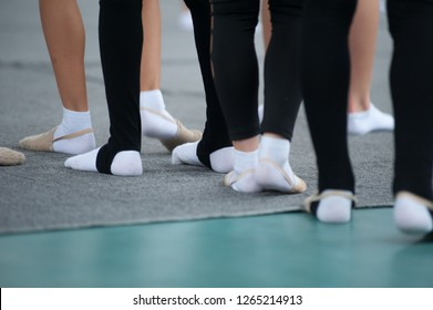 Close up of feet of young gymnast in black leggins and white socks on the floor in the dance studio. Close up of feet of young ballerinas at the gym club