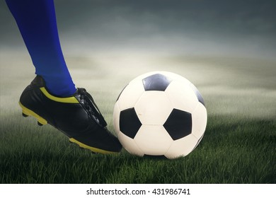 Close up of feet's soccer player kicking the ball at field under cloudy sky