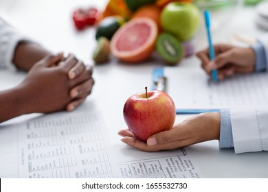 Close up of female afro doctor holding big fresh red apple, black lady having session with dietologist