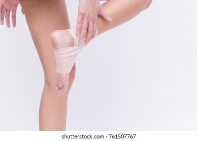 Close up of female ankle with gauze bandage or women's ankle get injured or painful and touching her ankle on Achilles tendon area (joint tarsal  bone pain or muscle pain concept)