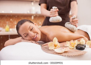 Close up of female arms of masseuse massaging client with textile massage spa equipment. The woman is lying and relaxing. She closed her eyes with joy and smiling