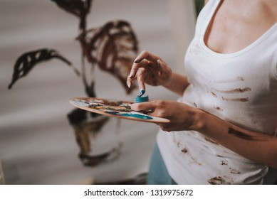 Close up of female artist standing in white dirty sleeveless shirt and holding an artist palette wheil putting her finger into the ble paint jar