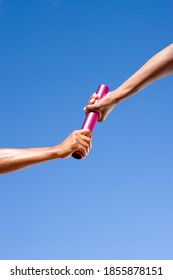 Close up of a female athlete passing a relay baton to her teammate on a bright, sunny day at an athletics competition
