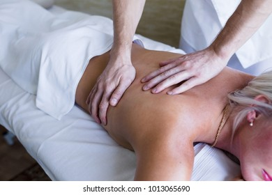 Close up of female back getting massage by male professional masseur. Body care, skin care, wellness, wellbeing, health, beauty treatment concept.