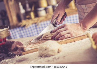 Close up of female baker hands cutting dough and making bread. Retro look.
