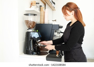Close up of female barista using modern beautiful coffee machine with vintage style black and chrome texture design to prepare cappuccino. Macro shot of coffee making equipment. Copy space, background