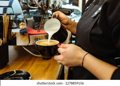 Close up of female barista's hands pouring warm milk in black cup for making coffee cappuccino art. Skillful staff and real work concept.