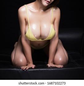 Nahaufnahme großer weiblicher Brüste in gelbem Bikini. Einzeln auf schwarzem Hintergrund