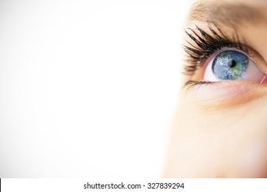 Close up of female blue eye against earth