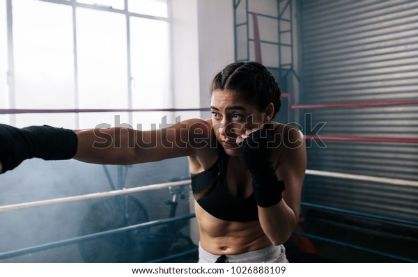 Close up of a female boxer training inside a boxing ring. Boxer practicing her moves at a boxing studio.