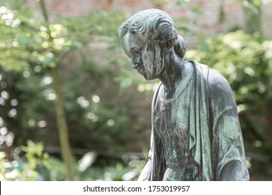 Close up of a female bronze statue of a woman with short hair with cross and cardigan in a park, Germany