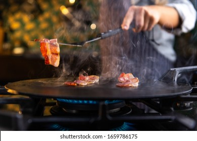 Close up of a female chef flipping a sizzling, hot piece of bacon on a kitchen stove.