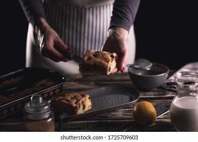 Close up of female chefs hands servicing slice of cake with cherries on dark background.