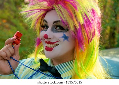 Close up of a female circus clown with face makeup.