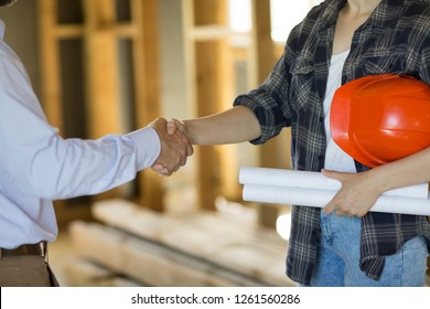 Close up of female contractor shaking hand of male client after matching all construction details and signing contract. Woman holding orange helmet under armpit and house plan in other hand.