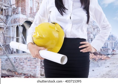 Close up of female contractor standing at the construction site while holding a blueprint and helmet