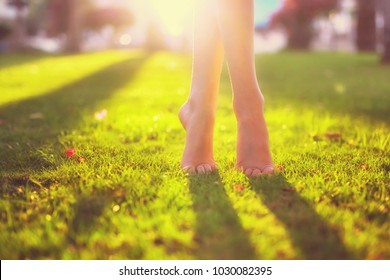 Close up female crossed legs walking on the grass