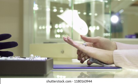 Close up of female customer choosing ring at the jewelry boutique. Woman's hand trying on different finger rings. Seller's hand in black glove putting jewels on the pad