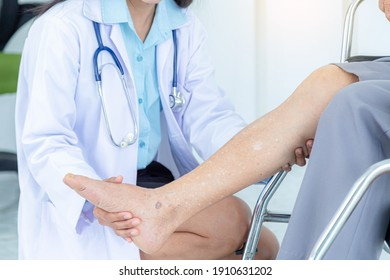 Close up of female doctor examining senior woman's leg iwhile sitting on wheelchair. Elderly patient care and health care, medical concept.