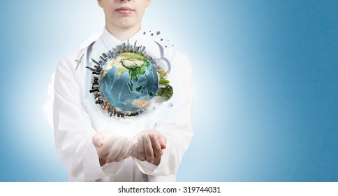 Close up of female doctor holding Earth planet in hands. Elements of this image are furnished by NASA