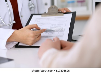 Close up of a female doctor pointing into an application form while consulting patient. Medicine and health care concept