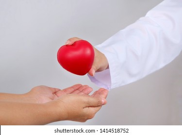 Close up female doctor's hand in white coat holding red heart for give to empty patient's hands with blurred gray wall background, caring and health insurance concept