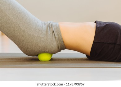 Close up of female doing self-massage technique applying tennis balls for back pain relief, working out on fitness mat on grey studio floor background, closeup.