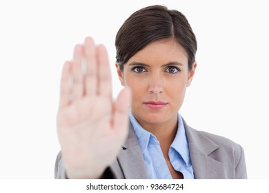 Close up of female entrepreneur signalizing stop against a white background
