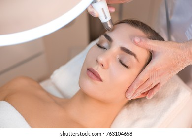 Close up of female face having laser rejuvenating treatment. Cosmetologist hand lifting equipment over her forehead. Beauty concept